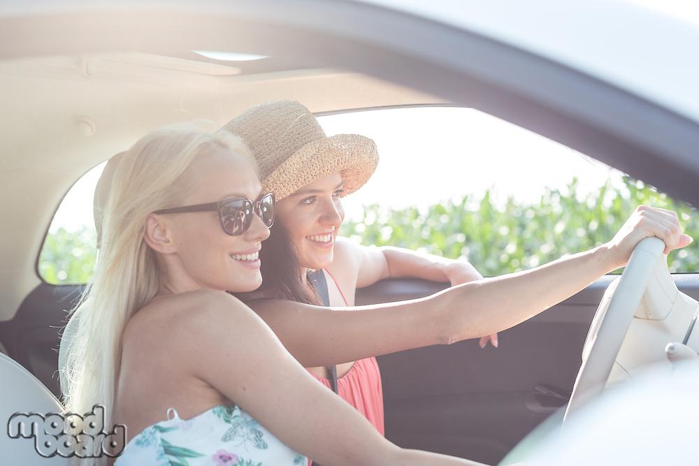 Happy female friends enjoying in car on sunny day