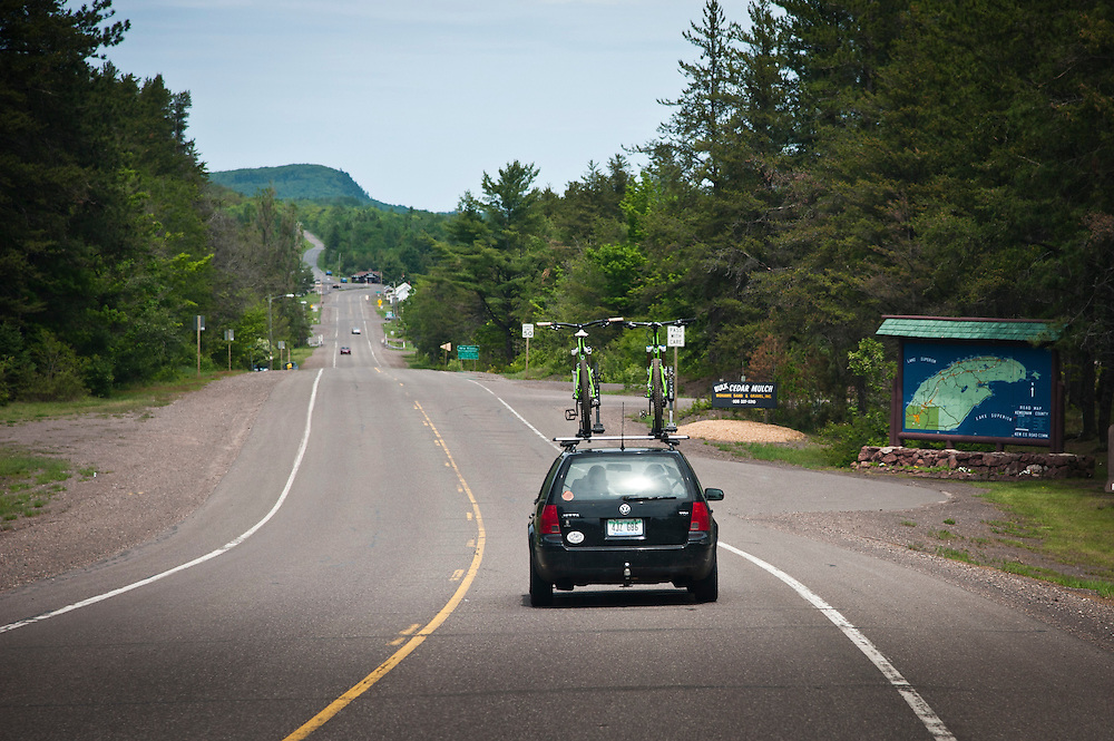 A vehicle with mountain bikes on top travels U.S. 41 on the Keweenaw Peninsula enroute to Copper Harbor Michigan.