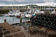 A local fisherman using a jetwash hoses down the seawater off shellfish pots overlooking the harbour, on 14th July 2017, at Scarborough, North Yorkshire, England.