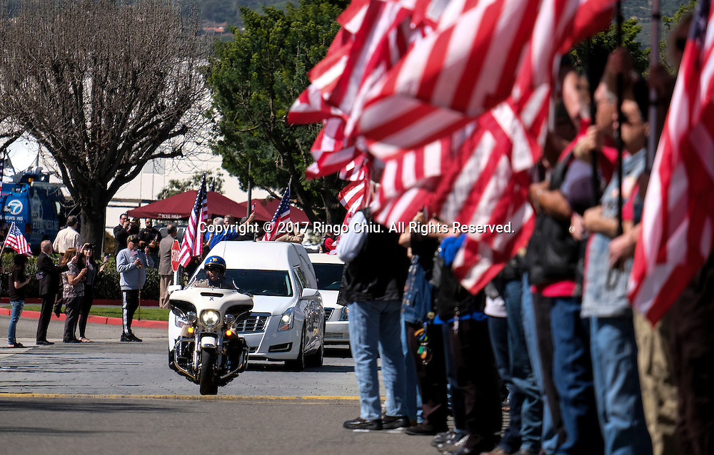 A police motorcycle leads the hearse carrying the body of Whittier Police Officer Keith Boyer arrives at Rose Hills Memorial Park in Whittier, Calif., Friday March 3, 2017. Boyer, who was fatally shot after responding to a traffic crash, was remembered today by thousands of law enforcement officers, friends and family as a dedicated public servant, talented drummer, loving friend and even a ``goofy'' dad.(Photo by Ringo Chiu/PHOTOFORMULA.com)<br />