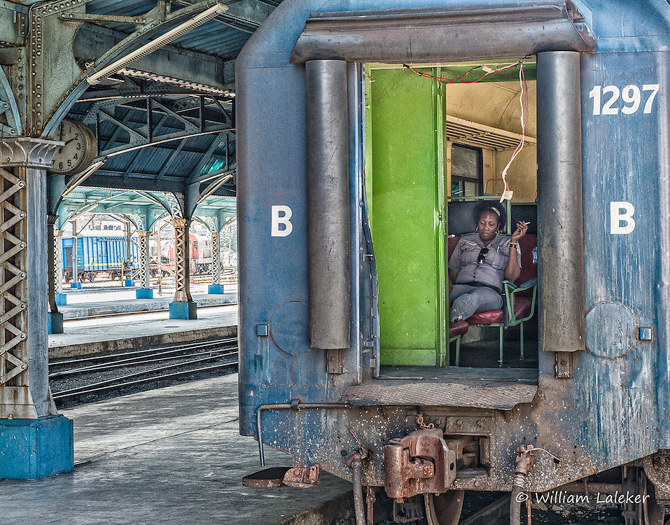 A worker for the Cuban railway (Ferrocarriles de Cuba) takes a smoke break in an old rail car still in use.