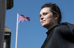 © Licensed to London News Pictures. 18/04/2018. At Somerset House in London to mark Earth Day 2018. Artist Lauren Bowker of studio The Unseen stands in sight of Choropleth, her new flag raised above Somerset House in London, ahead of an afternoon of free events to mark Earth Day on Sunday 22nd April. The flag changes colour as it reacts in real-time to London's air quality. The iconic colours of the Union Jack will transform, from red, white and blue to smoggy greys and sooty blacks, according to changes in the city's atmosphere, making the invisible visible. Photo credit: Peter Macdiarmid/LNP