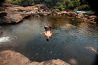 A young man jumps into a pool near a waterfall in Koh Kong, Cambodia.