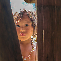 H'mong girl peeking through the crack in a house, Laos.