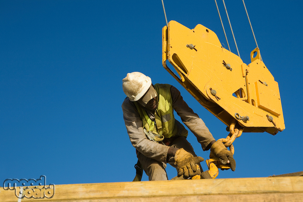 Workman secures harness for hook block