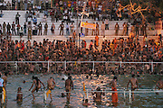 Pre-dawn swim of nagas on the banks of the Shipra River on an auspicious day for bathing during the Kumbh Mela festival, Ujjain, Madhya Pradesh, India. The Kumbh Mela festival is a sacred Hindu pilgrimage held 4 times every 12 years, cycling between the cities of Allahabad, Nasik, Ujjain and Hardiwar. Participants of the Mela gather to cleanse themselves spiritually by bathing in the waters of India's sacred rivers. Past Melas have attracted up to 70 million visitors.