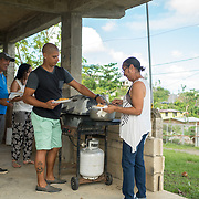 NOVEMBER 23 - TOA ALTA, PUERTO RICO - <br /> Angel Joel Alvarez, 34, serves Thanksgiving lunch with a turkey  cooked using a gas BBQ  grill in his mother in law's garage in the Comunidad Las Acerolas. The house has been without power since Hurricane Maria and it's sheltering several family members. Nancy Ojeda, 62, the mother in law, right, Max Ojeda, 59, and Michelle Vazquez Ojeda, 21 are getting food.<br /> (Photo by Angel Valentin/FREELANCE)