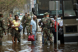 01 Sept, 2005. New Orleans, Louisiana.<br /> Mass evacuation begins. Exhausted former residents of the Superdome 'shelter of last resort' wade through flood water to get to the first busses evacuating people from New Orleans to destinations unknown.<br /> Photo©; Charlie Varley/varleypix.com