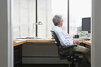 Business man sitting at desk in office side view