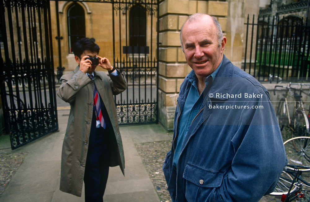A portrait of Australian-born, Clive James as he is recognised and photographed by a Japanese tourist, on 20th January 1990 in Cambridge UK. Clive James AO CBE FRSL (b1939) is an Australian author, critic, broadcaster, poet, translator and memoirist, best known for his autobiographical series Unreliable Memoirs, for his chat shows and documentaries on British television and for his prolific journalism. He has lived and worked in the United Kingdom since 1962.
