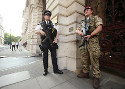 """A police officer and a soldier on duty outside the Foreign and Commonwealth Office, London, as armed troops have been deployed to guard """"key locations"""" under Operation Temperer, which is being enacted after security experts warned the Government that another terrorist attack could be imminent."""
