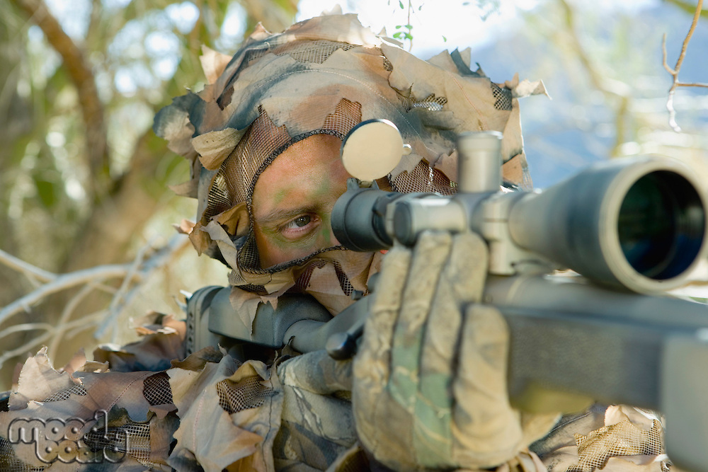 Soldier aiming through gunsight outdoors (close-up)