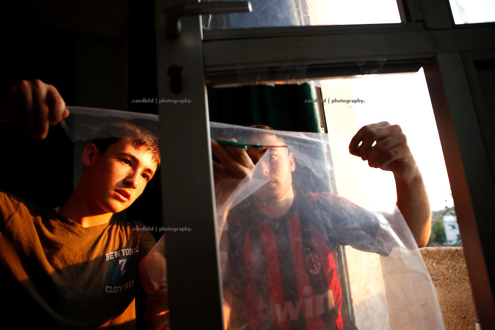 The two brothers Ahmad and Wissam taping plastic sheets into window and door frames in their families home. Almost all of the windows bursted off when Koreen was shelled by the regime forces.<br />