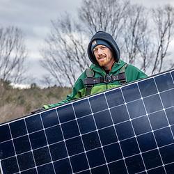 A PV Squared employee (Ephraim Wickline) installing solar panels on the roof of a barn in Shelburne, Massachusetts.