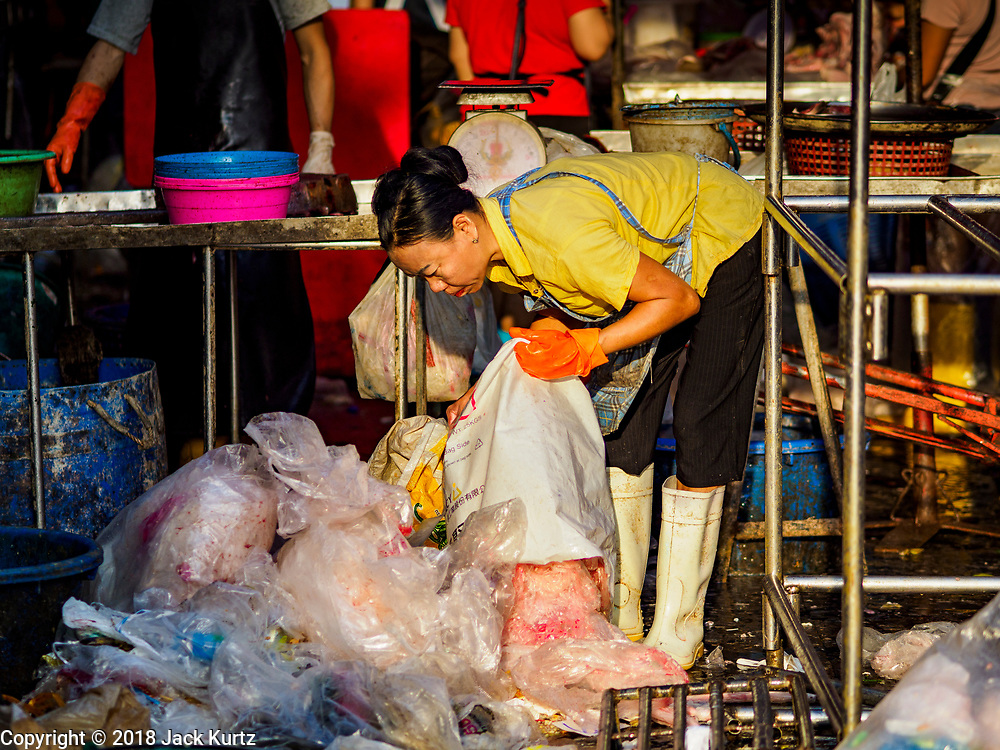 """04 DECEMBER 2018 - BANGKOK, THAILAND:  A worker sorts discarded single use plastic bags in Khlong Toei market. The issue of plastic waste became a public one in early June when a whale in Thai waters died after ingesting 18 pounds of plastic. In a recent report, Ocean Conservancy claimed that Thailand, China, Indonesia, the Philippines, and Vietnam were responsible for as much as 60 percent of the plastic waste in the world's oceans. Khlong Toey (also called Khlong Toei) Market is one of the largest """"wet markets"""" in Thailand. December 4 was supposed to be a plastic free day in Bangkok but many market venders continued to use plastic.    PHOTO BY JACK KURTZ"""