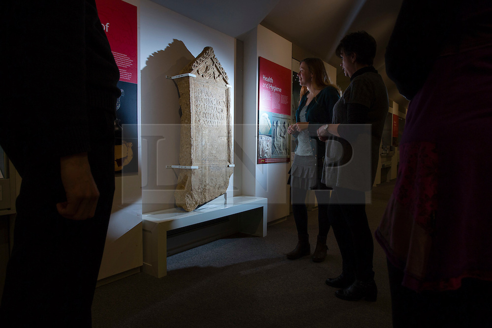 """© Licensed to London News Pictures 25/01/2016, Cirencester, UK. Museum staff look at a unique Roman tombstone, found in February 2015, here on display for the first time at Corinium Museum in Cirencester. The tombstone was found near skeletal remains thought to belong to the person named on its inscription, making the discovery unique. After being found during excavation works on a former site of a garage, archaeologists said they believed it marked the grave of a 27-year-old woman called Bodica. Other theories point to it possibly belonging to a couple - as skeletal remains of women were found nearby.<br /> The inscription reads """"To the shades of the dead, Bodicacia spouse lived 27 years"""". Photo Credit : Stephen Shepherd/LNP"""