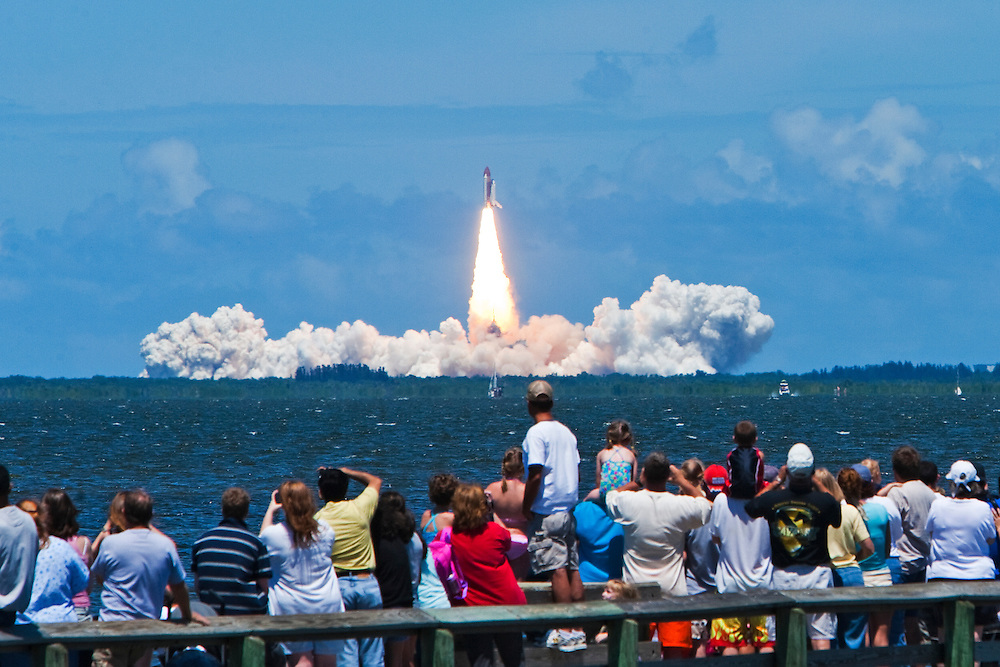 TITUSVILLE, FL - JULY 4:  Onlookers watch Space Shuttle Discovery lift off of pad 39-B across the Indian River from Titusville, Florida, July 4, 2006. Previous launch attempts were scubbed due to the weather. This will be NASA's second shuttle launch since the Space Shuttle Columbia Disaster in 2003. (Photo by Matt Stroshane/Getty Images)