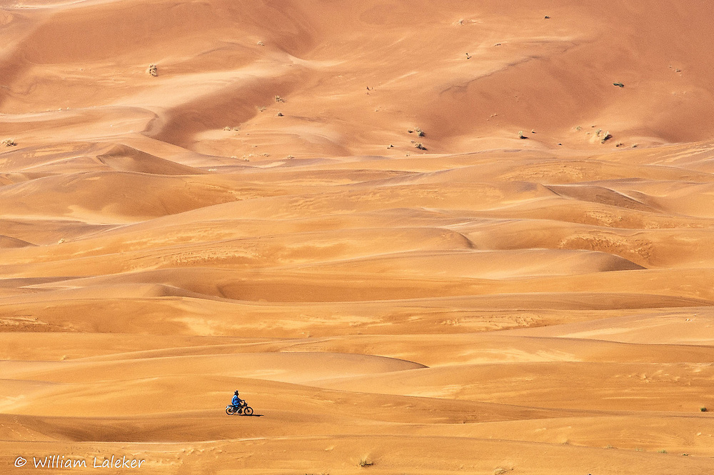 A berber rides across the desert on a motorbike.