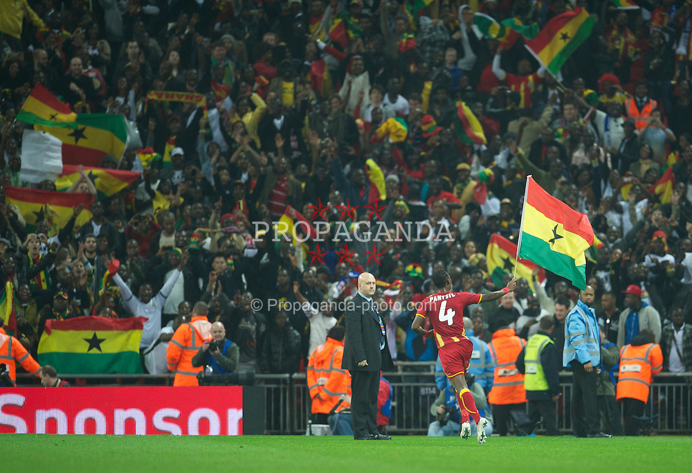 LONDON, ENGLAND - Tuesday, March 29, 2011: Ghana's John Pantsil celebrates with his national flag after his side score a dramatic late injury time equalising goal against England during the international friendly match at Wembley Stadium. (Photo by David Rawcliffe/Propaganda)