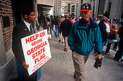 An African-American Georgia flag protestor holds his placard to a white passer-by before the Atlanta Braves World Series baseball victory parade, on 5th November 1995, in Atlanta, Georgia USA.. James Coleman brought this action to enjoin the flying of the Georgia state flag over Georgia's state office buildings. Coleman, an African-American, alleges that the flying of the Georgia flag, which incorporates the Confederate battle flag emblem, violates his constitutional rights to equal protection and freedom of expression.