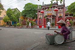 A vietnamese woman wearing a conical hat sells some food on the sidewalk in front of a pagoda's gate. Hoi An, Vietnam, Asia