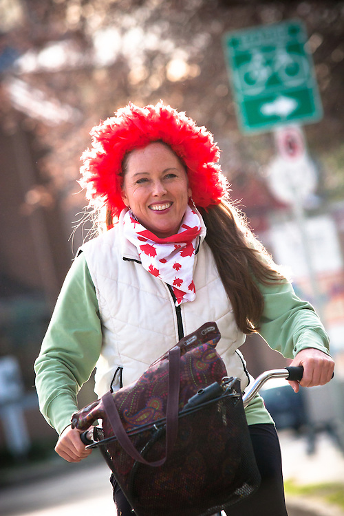 A woman cycles towards Downtown wearing a red wig.<br /> <br /> Tens of thousands of people in Vancouver took to the streets on Sunday 28th February 2010 to celebrate Canada's 3-2 overtime win over the United States for the gold medal in men's Olympic hockey...Traffic came to a halt in and around the downtown of the host city for the Winter Games following the dramatic finish to the match, which featured Sidney Crosby scoring to secure the victory on the final day of Olympic competition.
