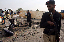 61056906<br /> Security officers inspect the blast site in southern Pakistani port city of Karachi, Feb. 13, 2014. At least 11 policemen were killed and 47 others injured when a suicide bomber rammed his explosive-laden car into a police bus in Karachi Thursday morning, police said, Thursday, 13th February 2014. Picture by  imago / i-Images<br /> UK ONLY