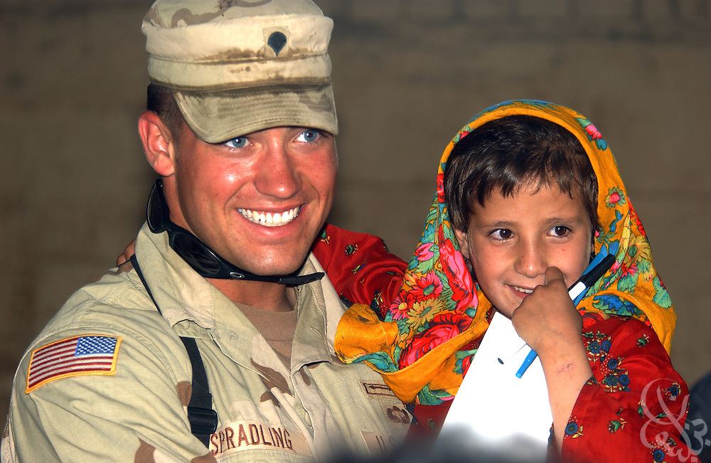 U.S. Army 18th Airborne Corps HSC SPC Derek Spradling, from Maryville, Tennessee, holds a young Afghan orphan girl July 10, 2002 at the Charikar Childrens Orphanage in Charikar, Afghanistan. Military civil affairs personnel handed out school supplies, toys, and candy to nearly 100 young Afghan boys and girls who live at the orphanage, which is located near the Bagram Airbase.