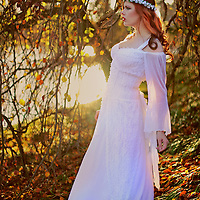 Profile of a pretty young woman wearing a white wedding dress with a fantasy outdoor background and pretty lighting