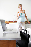 Young woman standing in kitchen by laptop and satchel focus on laptop