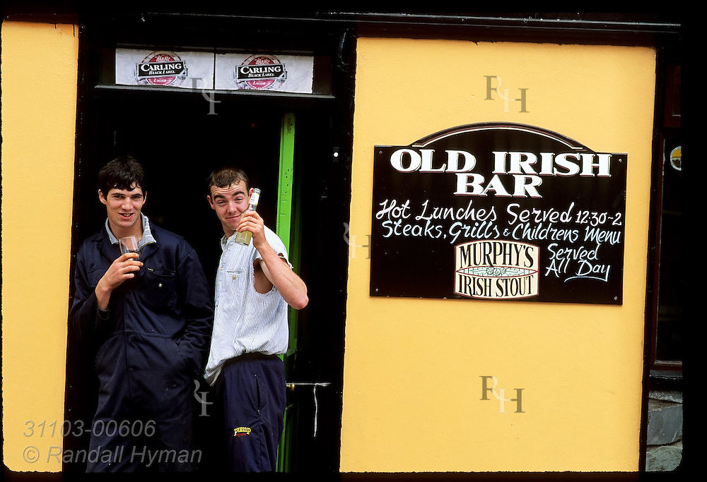 Two young men raise a toast to the camera as they stand outside pub in Castletownbere, Beara Peninsula, Ireland.