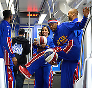 "The Harlem Globetrotters' Brawley ""Cheese"" Chisholm, center, balances with one leg inside a moving Atlanta Streetcar during the team's tour of downtown sights on their day off, Monday, March 9, 2015, in Atlanta. David Tulis / AJC Special"