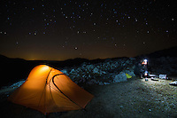 Hiker (Dan Dinu) heating up water beside his tent under starry sky over a rocky limestone ridge in Mehedinti Plateau Geopark, Geoparcul Platoul Mehedinți, Romania.