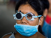 "22 JANUARY 2018 - GUINOBATAN, ALBAY, PHILIPPINES: A woman in an evacuation center in Guinobatan wears a face mask while she gets her eyes checked during a clinic at the shelter. Several communities in Guinobatan were hit ash falls from the eruptions of the Mayon volcano and many people wore face masks to protect themselves from the ash. There were a series of eruptions on the Mayon volcano near Legazpi Monday. The eruptions started Sunday night and continued through the day. At about midday the volcano sent a plume of ash and smoke towering over Camalig, the largest municipality near the volcano. The Philippine Institute of Volcanology and Seismology (PHIVOLCS) extended the six kilometer danger zone to eight kilometers and raised the alert level from three to four. This is the first time the alert level has been at four since 2009. A level four alert means a ""Hazardous Eruption is Imminent"" and there is ""intense unrest"" in the volcano. The Mayon volcano is the most active volcano in the Philippines. Sunday and Monday's eruptions caused ash falls in several communities but there were no known injuries.    PHOTO BY JACK KURTZ"