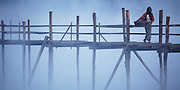 Woman crossing Thandwe river on U Wa wooden bridge, morning mist and fog