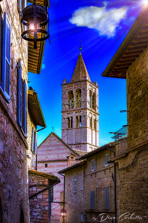&ldquo;The bell tower of Santa Chiara in Assisi rises high in the sky&rdquo;&hellip;<br /> <br /> After a progressive but slow assent up to the mountaintop of Assisi, I took time to pause, look over my shoulder, and truly appreciate all I had seen.  God always seemed to illuminate my forward path; however, He also left a glow of remembrance from where the journey began. This evening view is of the campanile from the Basilica di Santa Chiara. This 13th-century church houses the relics of St. Clare, friend and prot&eacute;g&eacute; of St. Francis of Assisi, and the 12th-century crucifix that spoke to St. Francis at San Damiano. The churches, Basilicas, Duomos, and all the spiritual history of this tiny hilltop village, force one to realize the blessings of the Saints who traversed the same footsteps as we walk today.  It is remarkable to imagine that seven Saints originated from Assisi over a 15 century period.  What a great percentage of the blessed from such a small town!  Assisi is perhaps one of the most visited pilgrimage areas in the world, and people from all races and religions come here to experience and find the peace which has blessed so many.  They say that one can almost hear all the prayers lifted up from the walls of this most spiritual of places.
