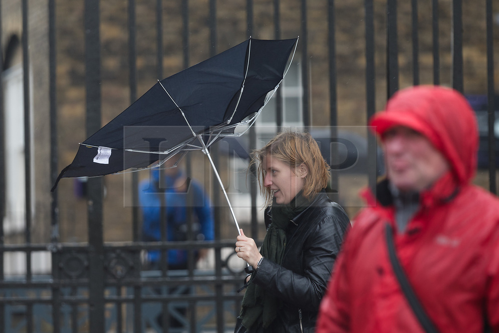 © Licensed to London News Pictures. 30/04/2018. London, UK. A woman walks along with her umbrella turned inside out by the wind during wet and windy weather at the top of the hill in Greenwich Park in London. The capital has been experiencing heavy rain and windy weather today. Photo credit: Vickie Flores/LNP