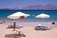 Umbrellas on the beach at Kitroplatia, a small cove outside Agios Nikolaos, Crete Greece