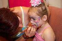 artist painting a butterfly on a girls face ready for a party