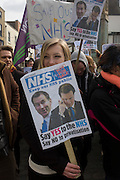 Young protesters demonstrate against coalition NHS privatisation plans in East Kent, during the enthronement for the new Archbishop of Canterbury, Justin Welby. Their protests are about coalition plans over the NHS, holding a placard in Butter Market in the centre of Canterbury. Health Secretary Jeremy Hunt and Conservative (Tory) Prime Minister David Cameron are parodied on the poster urging them to keep the country's National Health Service out of private hands, to keep it as a government organisation, run by Hunt and overseen by his boss, Cameron. The town of Canterbury hosted the enthronement of the Church of England's new Archbishop, allowing students to voice their concerns.