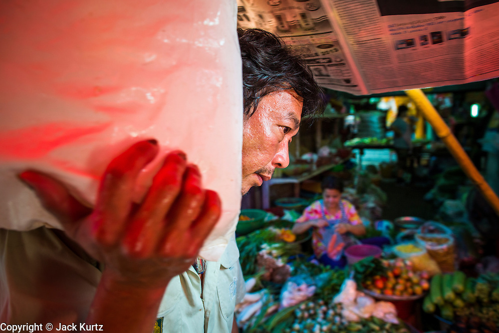 17 JANUARY 2013 - SAMUT SONGKHRAM, SAMUT SONGKHRAM, THAILAND:  A porter carries a bag of ice through the market in Samut Songkhram. Four trains each day make the round trip from Baan Laem, near Samut Sakhon, to Samut Songkhram, the train chugs through market eight times a day (coming and going). Each time market vendors pick up their merchandise and clear the track for the train, only to set up again when the train passes. The market on the train tracks has become a tourist attraction in this part of Thailand and many tourists stop to see the train on their way to or from the floating market in Damnoen Saduak.    PHOTO BY JACK KURTZ