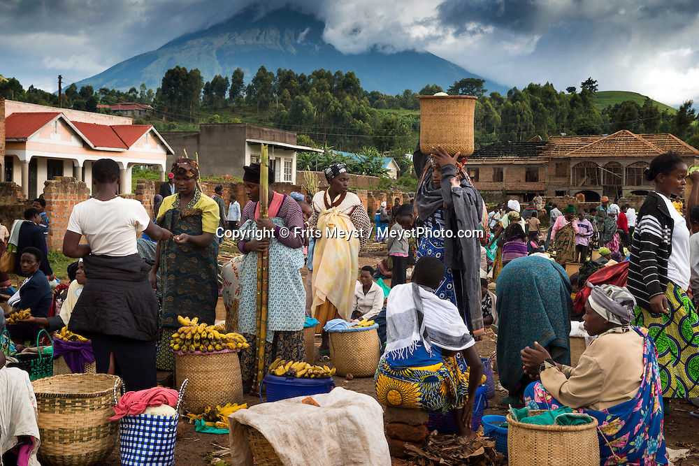 Kisoro, Uganda, April 2014. On market day in Kisoro, men, women and children walk up to 15km from their villages to sell their produce and bring back other shopping when they return. East of Lake Victoria, at the borders with Congo (DRC) and Rwanda, is where the East African savannah meets the West African jungle highlands and mountains. The route of our roadtrip becomes an epic journey over potholed mountain dirt roads, with a 4x4 vehicle, through some of Africa's most spectacular landscapes, various cultures, and National Parks. Photo by Frits Meyst / MeystPhoto.com