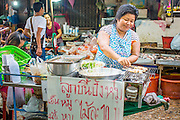 "03 OCTOBER 2012 - BANGKOK, THAILAND:     A snack vendor grills fish balls in Khlong Toey Market in Bangkok. Khlong Toey (also called Khlong Toei) Market is one of the largest ""wet markets"" in Thailand. Thousands of people shop in the sprawling market for fresh fruits and vegetables as well meat, fish and poultry every day.     PHOTO BY JACK KURTZ"