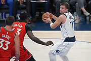 Dallas Mavericks point guard Luka Doncic (77) prepares to pass while being guarded by Toronto Raptors power forward Pascal Siakam (43) and center Marc Gasol (33) during an NBA basketball game, Saturday, Nov. 16, 2019, in Dallas. The Mavericks defeated the Raptors 110-102. (Wayne Gooden/Image of Sport)