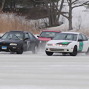 BRUNSWICK, Maine -- 2/23/13 --  Racers take a corner together on the New Meadows on Saturday afternoon. From left,  #97 Mike O'Donnell of Fairfield, Conn in his Nissan Altima, #43 Paul Glynn of Mass. in his 1987 VW Jetta and #23 Jeremy Hasbrouck of Berwick, ME in his 1997 Saturn SL2. Glynn finished 5th with 87 laps, O'Donnell finished third with 90 laps and Hasbrouck finished 9th with 79 laps. Photo by Roger S. Duncan.  .