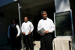 Waiters stand next to a menu board outside the Casa Mexico restaurant while they wait for the lunch crow to show.