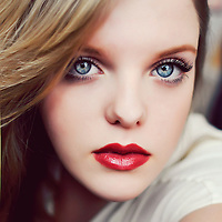 Glossy close up of young woman with blonde hair and very red lipstick looking into camera