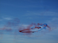 """Coloured smoke trails from French air forces aerobatic team """"La Patrouille de France"""" during an airshow rehearsal over the scenic cliff of Etretat, a Normandy coastal town in France. 23 September 2011."""