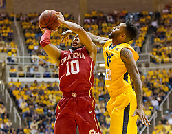 Feb 20, 2016; Morgantown, WV, USA; Oklahoma Sooners guard Jordan Woodard (10) shoots and is defended by West Virginia Mountaineers guard Tarik Phillip (12) during the first half at the WVU Coliseum. Mandatory Credit: Ben Queen-USA TODAY Sports