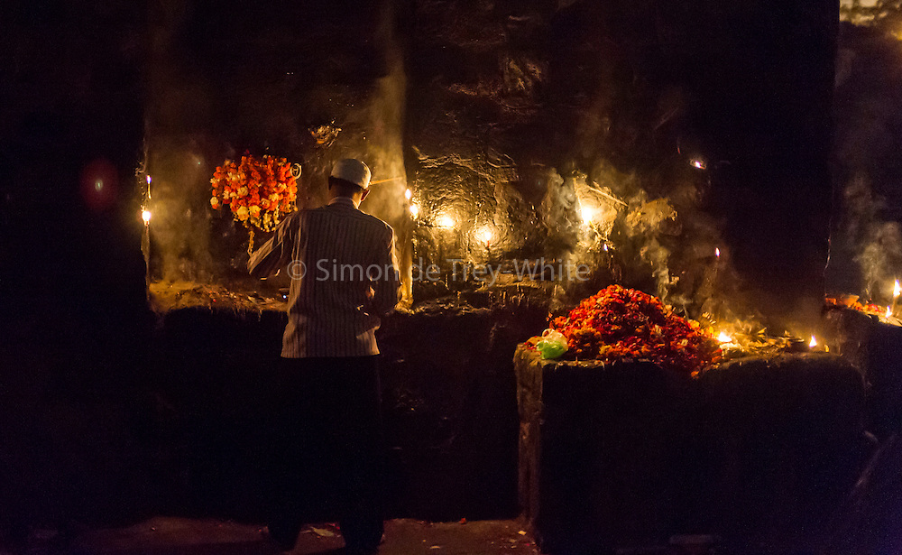 19th November 2015, New Delhi, India. A man tends a shrine dedicated to Djinn worship in the ruins of Feroz Shah Kotla in New Delhi, India on the 19th November 2015<br /> <br /> PHOTOGRAPH BY AND COPYRIGHT OF SIMON DE TREY-WHITE a photographer in delhi<br /> + 91 98103 99809. Email: simon@simondetreywhite.com<br /> <br /> People have been coming to Firoz Shah Kotla to pray to and leave written notes and offerings for Djinns in the hopes of getting wishes granted since the late 1970's. Jinn, jann or djinn are supernatural creatures in Islamic mythology as well as pre-Islamic Arabian mythology. They are mentioned frequently in the Quran  and other Islamic texts and inhabit an unseen world called Djinnestan. In Islamic theology jinn are said to be creatures with free will, made from smokeless fire by Allah as humans were made of clay, among other things. According to the Quran, jinn have free will, and Iblīs abused this freedom in front of Allah by refusing to bow to Adam when Allah ordered angels and jinn to do so. For disobeying Allah, Iblīs was expelled from Paradise and called &quot;Shayṭān&quot; (Satan).They are usually invisible to humans, but humans do appear clearly to jinn, as they can possess them. Like humans, jinn will also be judged on the Day of Judgment and will be sent to Paradise or Hell according to their deeds. Feroz Shah Tughlaq (r. 1351&ndash;88), the Sultan of Delhi, established the fortified city of Ferozabad in 1354, as the new capital of the Delhi Sultanate, and included in it the site of the present Feroz Shah Kotla. Kotla literally means fortress or citadel.